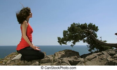 Woman yoga practices - A beautiful woman sits on a large...