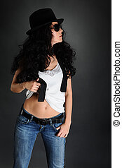 Portrait of a girl wearing sunglasses and a hat on a black...