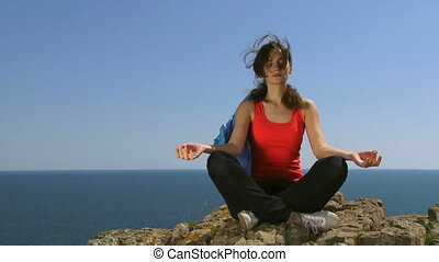 Woman practices yoga by the sea