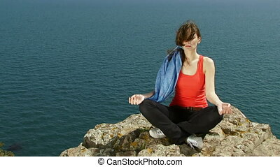 Woman is engaged in yoga - The beautiful woman sits on a...