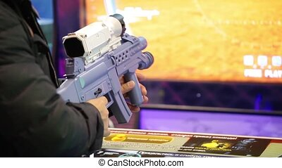 Man playing shooter video game in game center