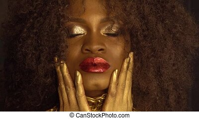 Close-up fashion portrait of young african american female model with gold glossy makeup. Face art. Black studio background