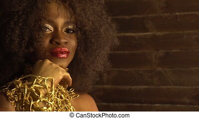 Beautiful young african american female model with gold glossy makeup. Face art. Black studio background