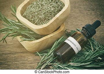 Rosemary essential oil in bottle and fresh rosemary on old...