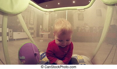 Child in children arena - Sitting in playpen child play toy