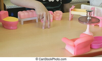 Children playing children's furniture at the table