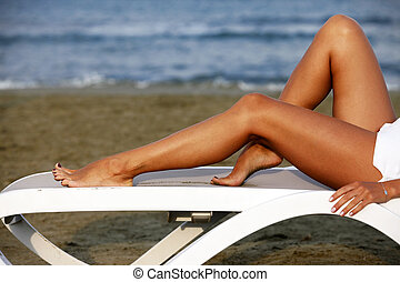 Woman relaxing in a chair on the Mediterranean beach...