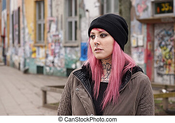 pierced and tattooed woman in front of graffiti covered...