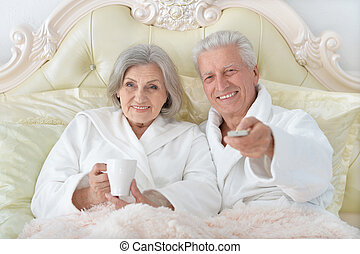 Senior couple in bed - happy Senior couple reading in bed...
