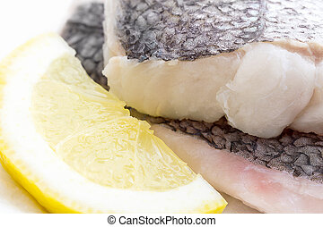 Hake fillet with skin and lemon, macro, as background, soft...
