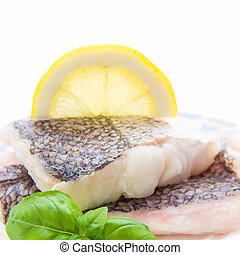 Hake fillet with skin and lemon, macro, isolated, soft focus