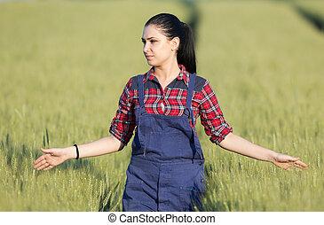 Happy farmer girl in wheat field