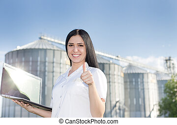 Woman agronomist in front of silo with thumb up - Young...