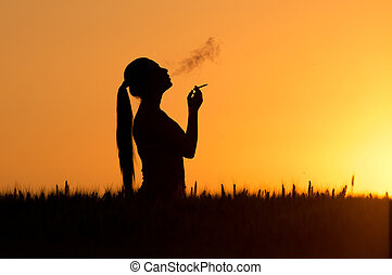 Smoking woman silhouette - Silhouette of young woman smoking...