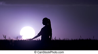 Woman in wheat field at dusk - Silhouette of young woman...