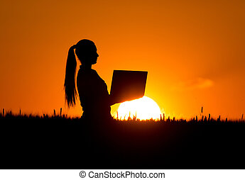 Woman with laptop in wheat field at dusk - Silhouette of...