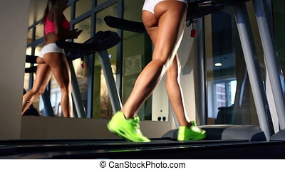 Beautiful woman's legs on treadmill
