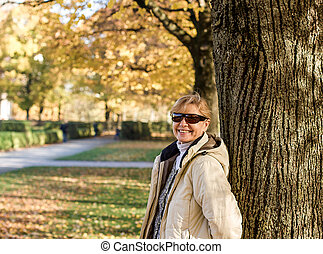 Mature, smiling woman in autumn park at tree