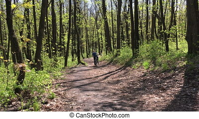 Boy riding a bike through the woods