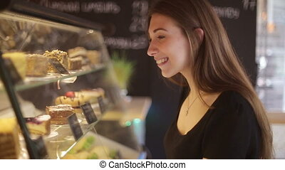 Beautiful female customer shopping showcase in a bakery store pointing at the dessert she is buying