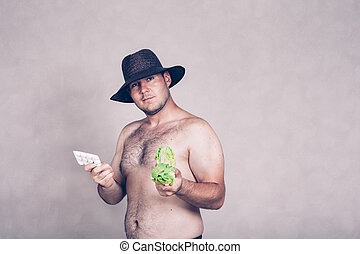 Naked corpulent man holding pharmaceuticals and vegetable