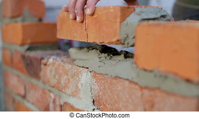 Work lays bricks on a construction site - Bricklayer Using a...