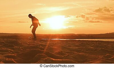 the setting sun on the sand beach ball man playing slow...