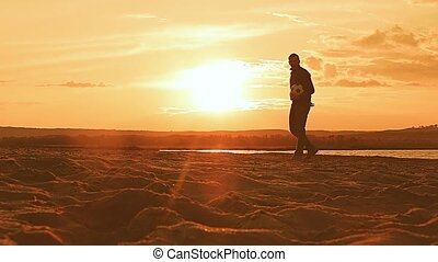 man against the sunset throws up the ball on the sand beach...