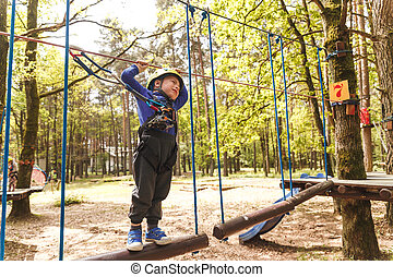 Young boy in helmet walks by pendant tree log at sunny...