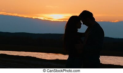 a woman with a man at sunset silhouette slow motion video