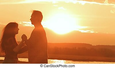 at sunset a man and woman dancing the waltz slow motion...