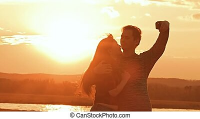 couple photographed against the backdrop of sunset slow...