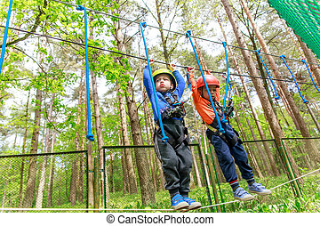 Twin brothers in helmet walks by rope at sunny summer day in...