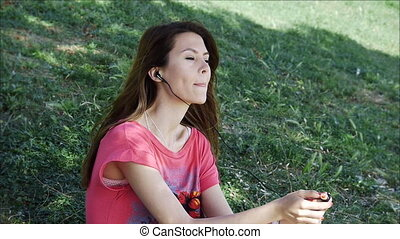 Young woman listening to music in park