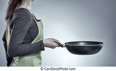 Woman chef with a wok - Woman chef holding a wok pan against...