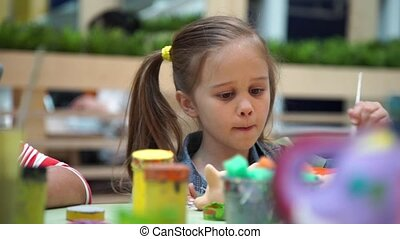 Little girl paints ceramic cat at the table - Girl paints...