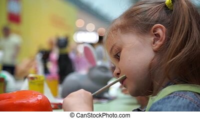 Little girl paints ceramic cat at the table