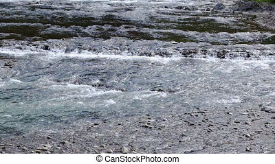 Close up of water stream with white and transparent bubbles,...