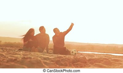 at sunset on the beach friends do selfie phone slow motion...