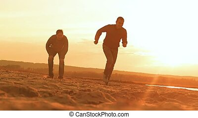 at sunset on the beach the men throw a soccer ball slow...