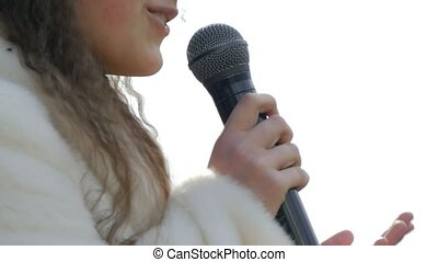 girl smiling speaks into the microphone slow motion video -...