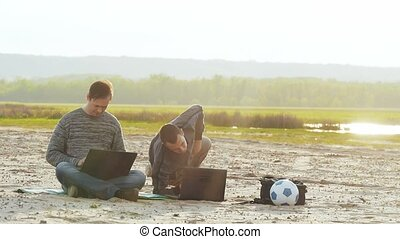 Two men with laptops on the sand slow motion video