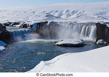 Frozen waterfall with clea blue water at late winter,...