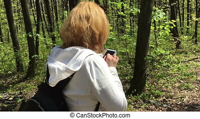 The girl in the woods writes a message on the phone. Slow motion