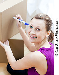 Smiling woman writing on a box at home