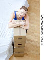 Cute woman unpacking box in the liv