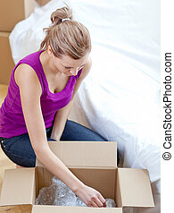 Courageous woman unpacking box in t