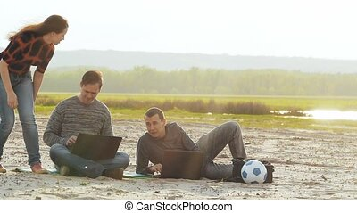 friends, two men and a woman with a laptop on the beach slow...