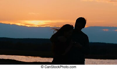 silhouette of a girl and a guy selfie slow motion video - at...