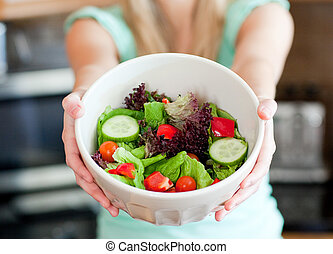 Young woman showing a salad in the kitchen